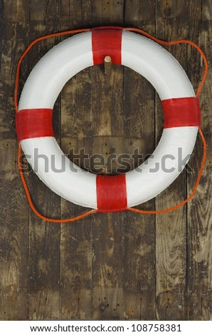 rescue wheel on a old board background - stock photo