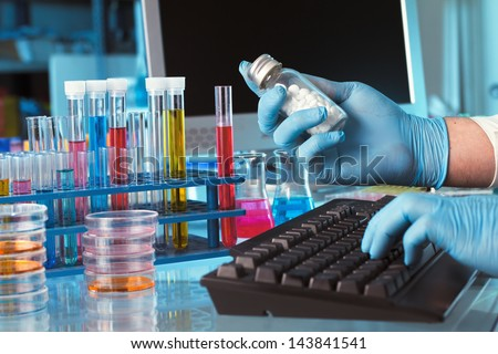 research chemist with a bottle of pills with logging data in the computer laboratory - stock photo