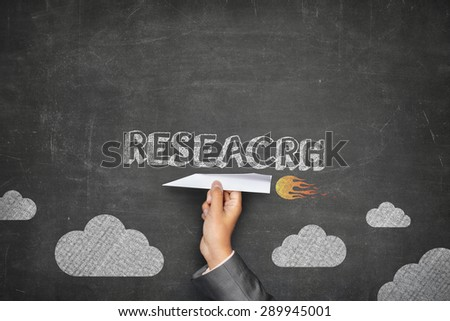 Research concept on black blackboard with businessman hand holding paper plane - stock photo