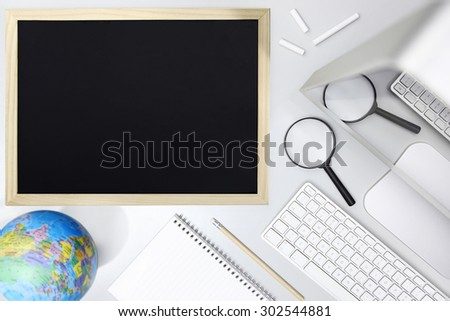 research concept, top view of desk with blackboard computer magnifying glass and globe map - stock photo