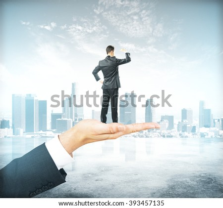 Research concept with businessman standing on palm, looking into the distance on misty city background - stock photo