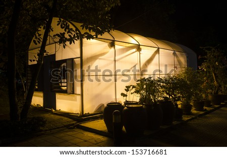 research greenhouse at university campus with lights on at dusk - stock photo