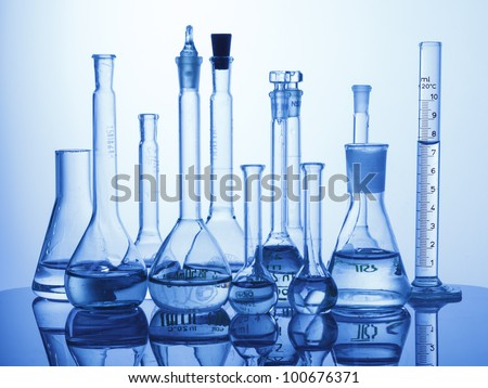 Research Lab assorted Glassware Equipment on blue background - stock photo