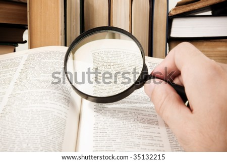 research (selective focus on some words of dictionary (center of magnifying glass)) - stock photo