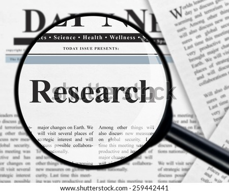 Research under magnifying glass - stock photo