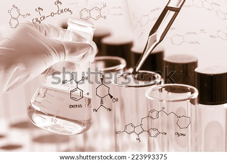 Researcher is dropping the reagent into test tube for reaction testing in chemical laboratory. - stock photo