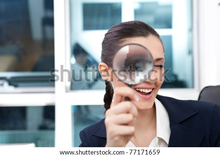 researching smiling business woman with magnifying glass to the eye - stock photo