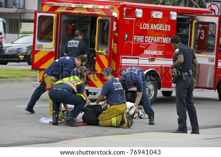 RESEDA, CALIFORNIA, USA - MAY 9: Firefighters help the victim of car accident on May 9, 2011 on Sherman Way in Reseda, California. - stock photo