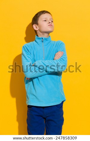 Resentful boy. Young boy posing with arms crossed. Three quarter length studio shot on yellow background. - stock photo