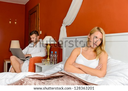 Resentful girl sitting bed room after fight boyfriend - stock photo