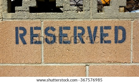 Reserved sign found on a brick wall. - stock photo
