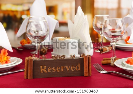 Reserved sign on restaurant table with empty dishes and glasses - stock photo