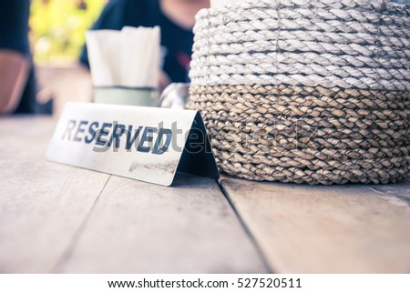 reserved table with tissue cup and potted plant
