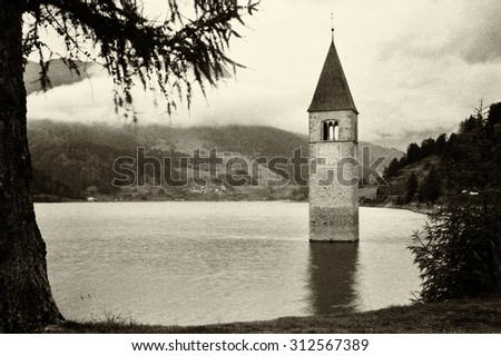 Resia, Italy: famous old bell tower on the lake - high noise added  - stock photo