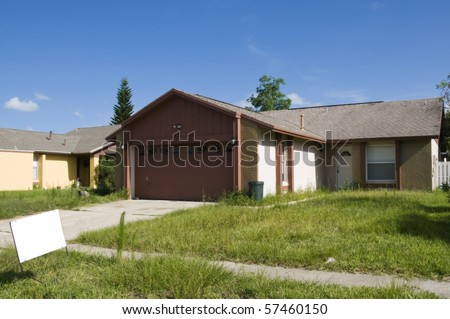 Resident abandoned due to foreclosure during recession with sign - stock photo