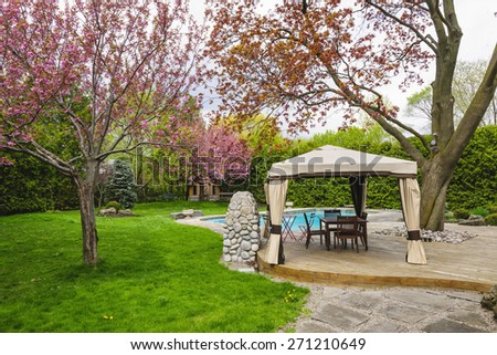 Residential  backyard with gazebo, deck, stone patio and swimming pool - stock photo