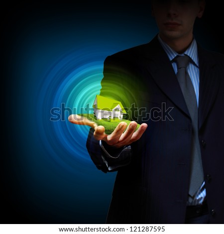 Residential building and a businessman holding it in his hands - stock photo