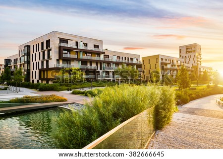 Residential building in the public green park during sunrise - stock photo