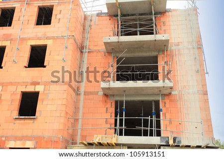 residential building under construction in red brick - stock photo