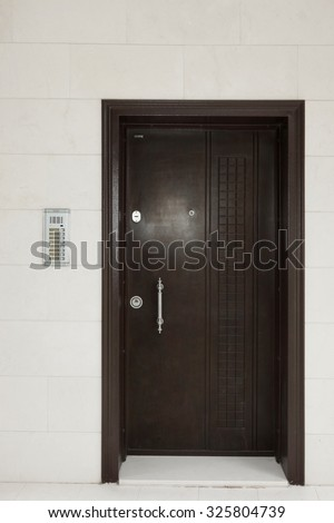 Residential Building White Wall With Iron Brown Door And Intercom System - stock photo