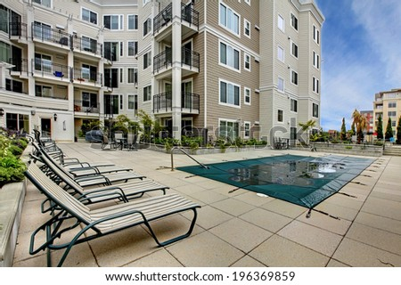 Residential building with swimming pool, patio area and deck chairs - stock photo