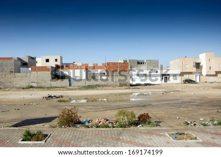 Residential buildings and typical dusty and dirty street full of garbage in Kairouan, Tunisia - stock photo