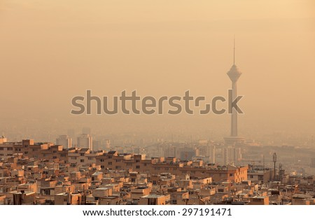 Residential buildings in front of Milad Tower in air-polluted skyline of Tehran illuminated with golden sunset. - stock photo