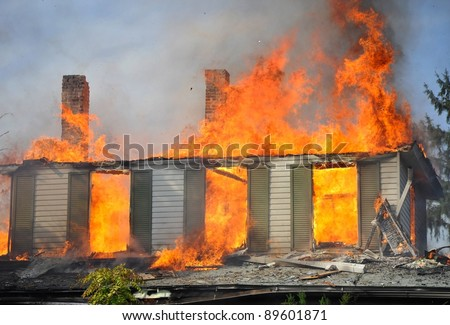 residential home on fire, fully involved, engulfed in orange fire and flames, concept disaster - stock photo