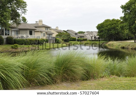 Residential homes by a tranquil pond.  The houses are on Hilton Head Island in South Carolina. - stock photo
