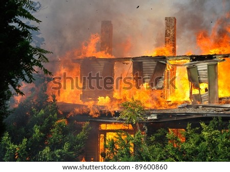 residential house in suburbs on fire, fully engulfed in flames - stock photo
