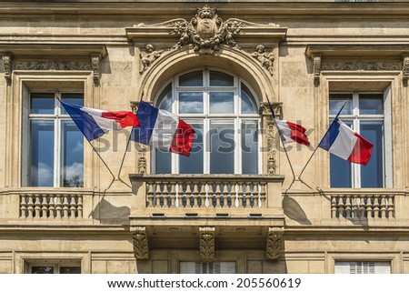 Residential house near Arc de Triomphe de l'Etoile decorated with the flags of France, on the French National Day (Bastille Day). - stock photo