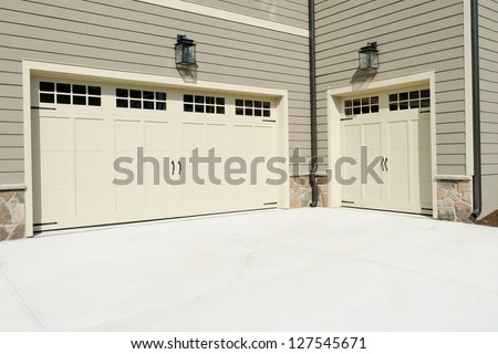Residential house three car garage doors - stock photo