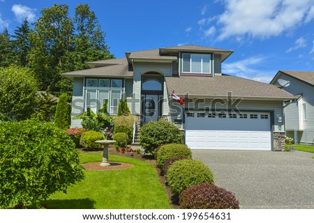 Residential house with garage on blue sky background.  - stock photo