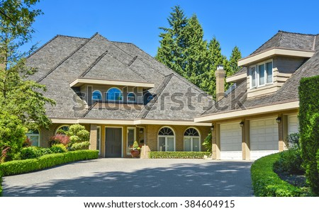 Residential house with massive roofs, green hedge in front on blue sky background. Family house with big roofs tiled by wooden shingles. House with detached garage for three parking lots. - stock photo