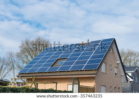 residential house with solar panels on the roof - stock photo
