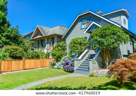 Residential house with the pathway over front yard lawn on blue sky background.