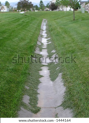 Residential storm drainage, poorly maintained - illustrates flooding threat due to clogged drainage systems. - stock photo