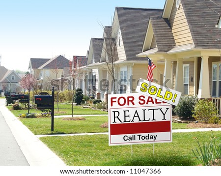 Residential street with a prominent SOLD sign - stock photo