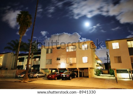 Residential street with apartment buildings at night in Los Angeles, California. - stock photo