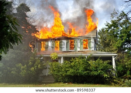 residential suburban home engulfed by fire - orange flames with smoke - stock photo
