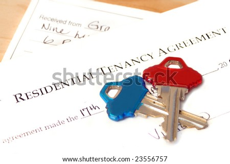 residential tenancy agreement document with blue and red keys on top and a rental cheque underneath - stock photo