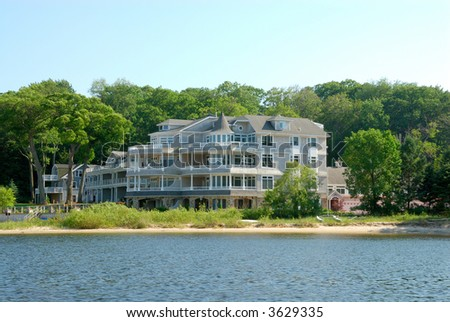 Residential Upscale Lakeside Home - Residential suburban home in an upscale waterfront neighborhood in the summertime. - stock photo