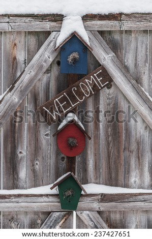Residential welcome sign, trimmed with  some light snow, hanging on a rough exterior fence gate..