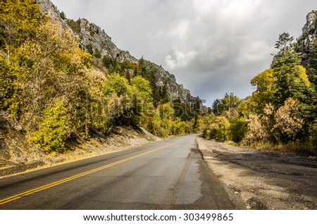 Residual clouds left from a lovely autumn shower leaving the road a bit wet and the foliage fresh - stock photo