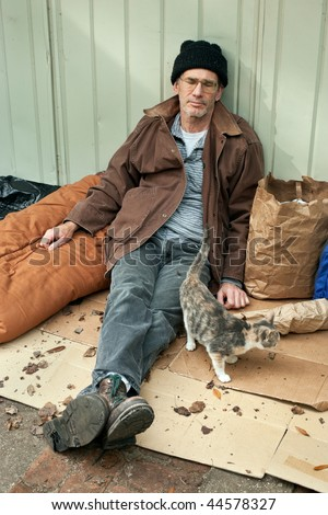 Resigned looking mature homeless man seated on the street with a friendly stray cat. - stock photo