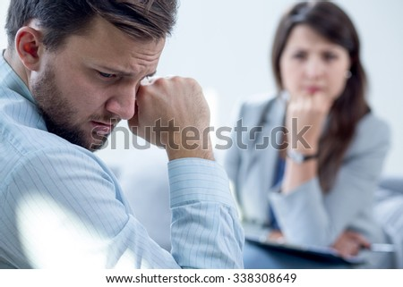 Resigned man receiving psychotherapy at psychiatrist's office - stock photo
