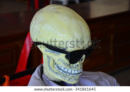 Resin skull wearing sunglasses - stock photo