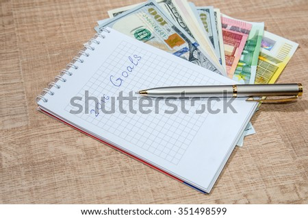 resolutions for new year 2016 with dollar and euro on wooden table