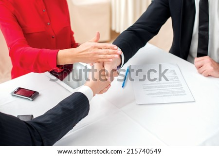 Resolve the dispute. Three successful and confident businesspeople shake hands. Businesspeople in formal dress sitting in an office at a desk close-up view of hands - stock photo