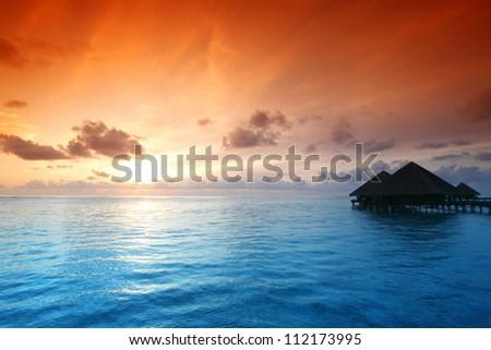 resort maldivian houses on sunrise - stock photo